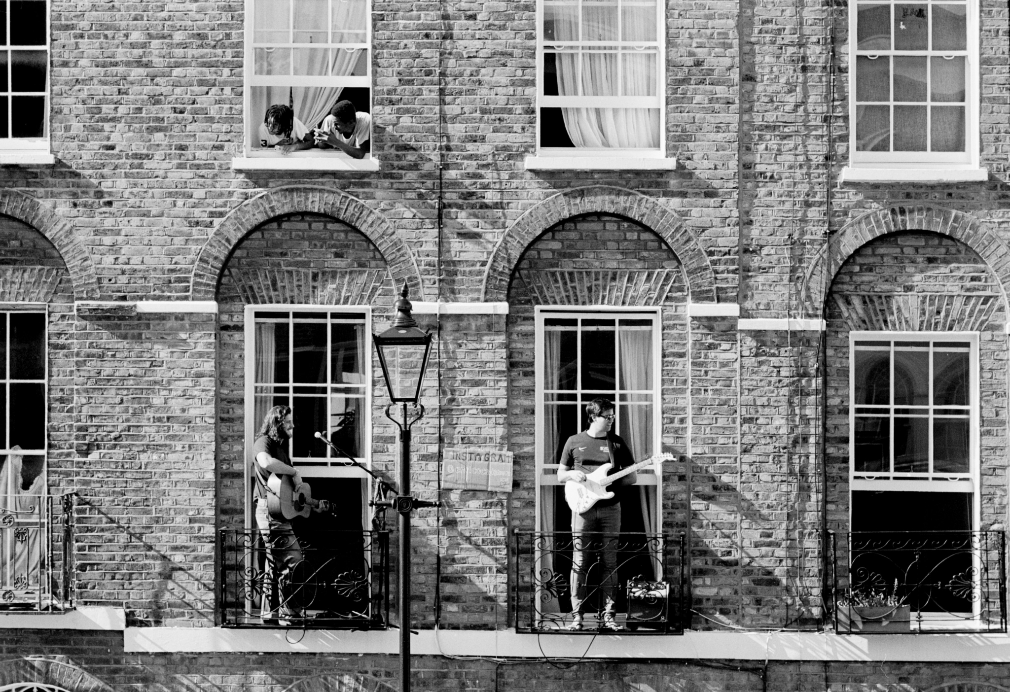 Boys playing guitar outside old houses