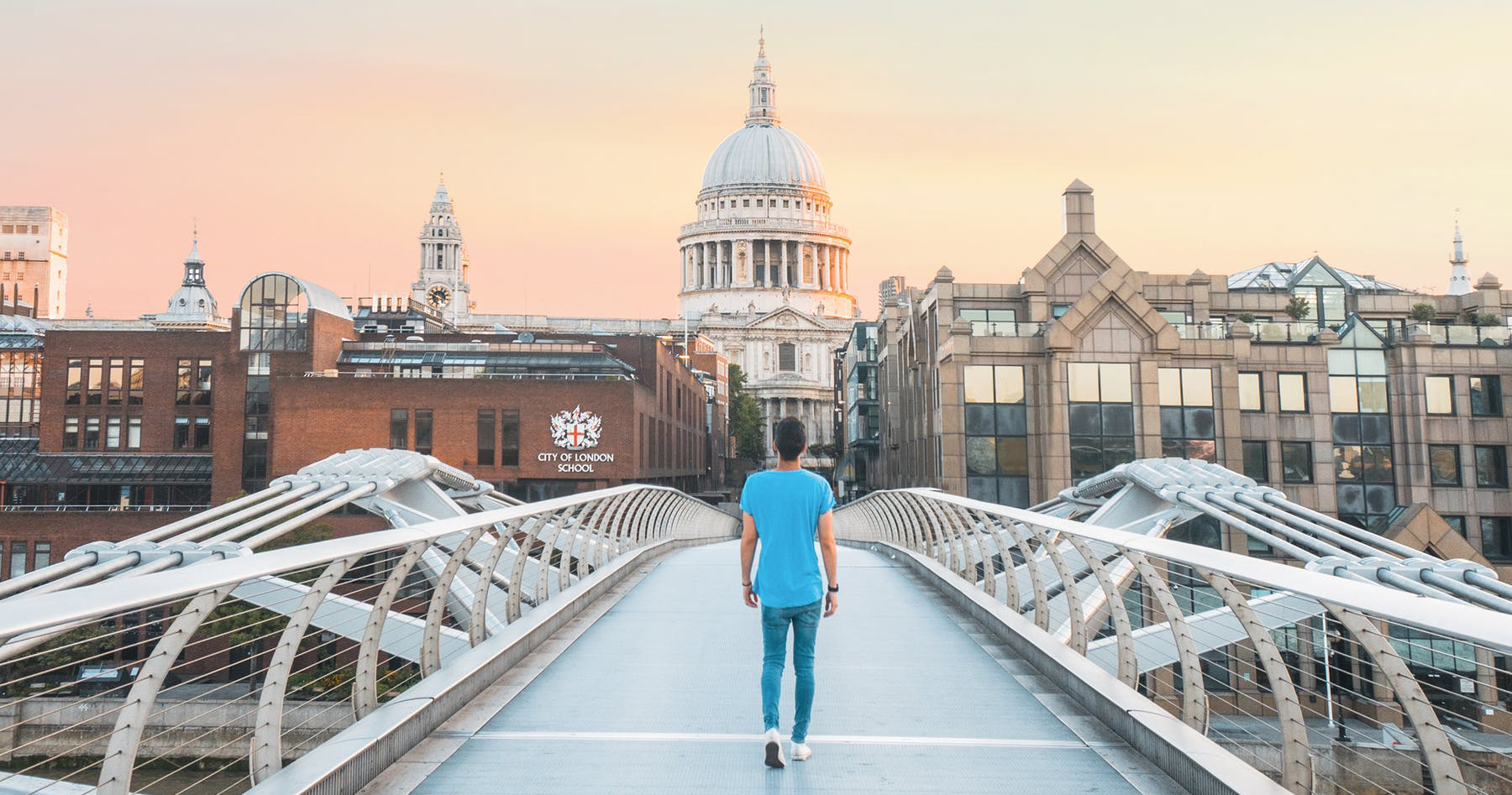 boy walking on the Millenium Bridge towards St Pauls Cathedral and the City of London School for Boys