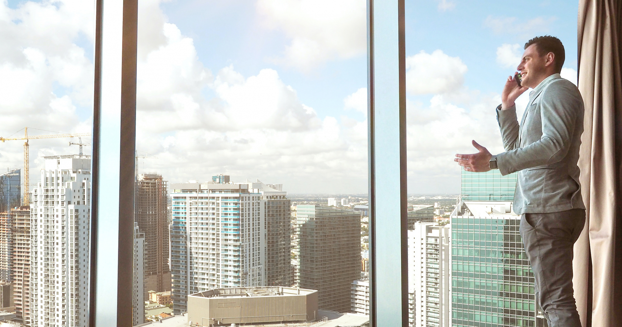 A property finder on the phone overlooking skyscrapers