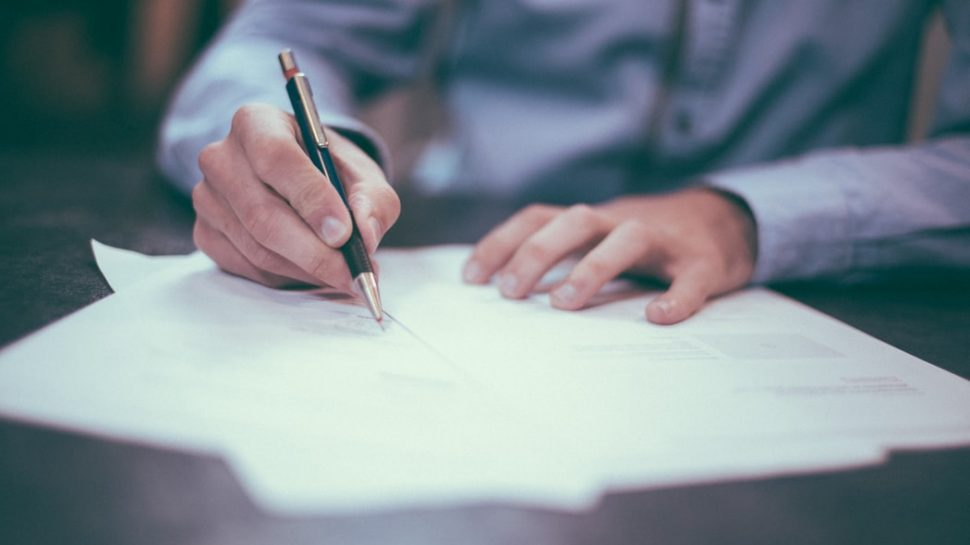 Someone signing a help to buy document